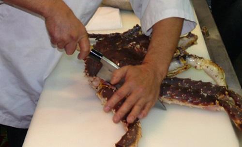 Используя нож Деба бренда Masahiro шеф-повар отрубает правую фалангу краба…